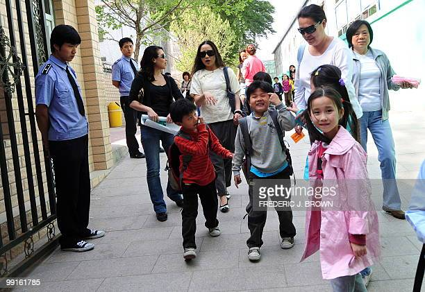Parents pick up their children at the end of the school day from an elementary school in Beijing on May 12 2010 as security guards stand at the...