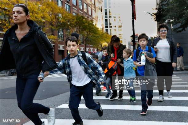 Parents pick up their children from Public School 89 near the scene where a truck plowed through a bike path in lower Manhattan on October 31 2017 in...
