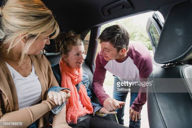 parents placing disabled daughter in the car - als stock photos and pictures