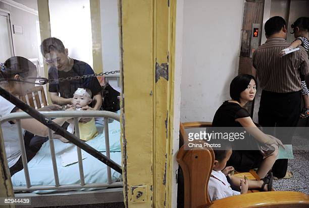 Parents play with a baby who suffers from kidney stones after drinking tainted milk powder at the Chengdu Children's Hospital on September 22 2008 in...