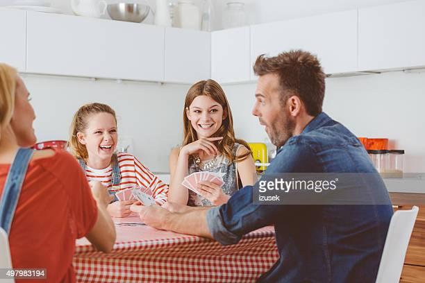 pais jogando cartas com suas filhas na cozinha - carta de baralho jogo de lazer - fotografias e filmes do acervo