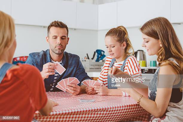 Parents playing cards with their daughters in the kitchen
