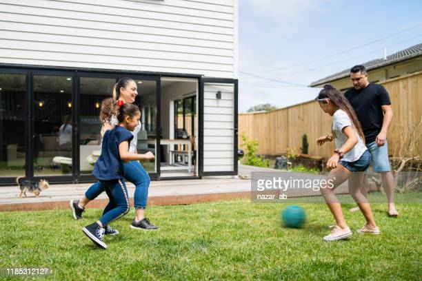 parents playing soccer with kids in backyard. - new zealand stock pictures, royalty-free photos & images