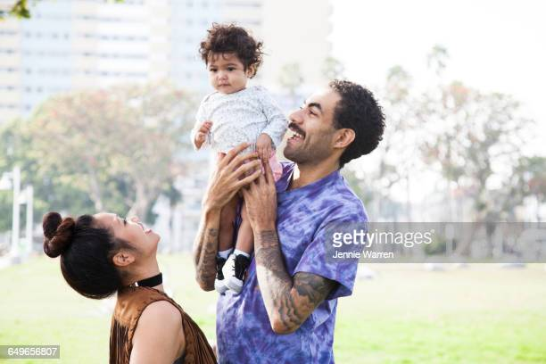 parents playing with baby son in park - black man holding baby stock photos and pictures