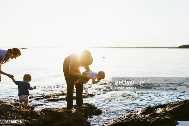 parents playing with children while standing on rocks at beach against clear sky during sunset - maine stock pictures, royalty-free photos & images