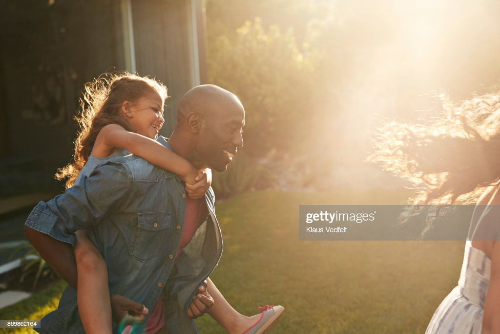 Parents playing with their kids in the garden : Stock Photo