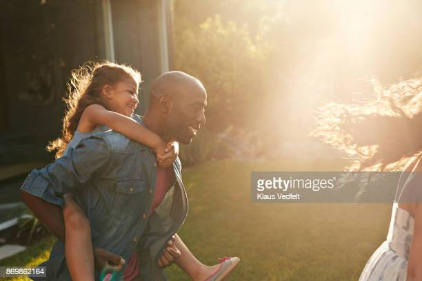 parents playing with their kids in the garden - piggyback stock pictures, royalty-free photos & images