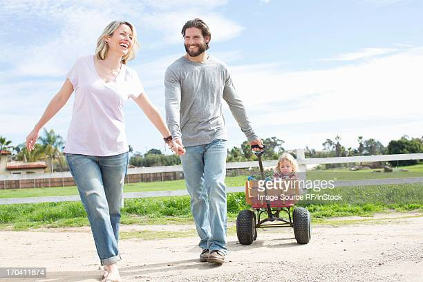 parents pulling son in wagon - toy wagon stock photos and pictures