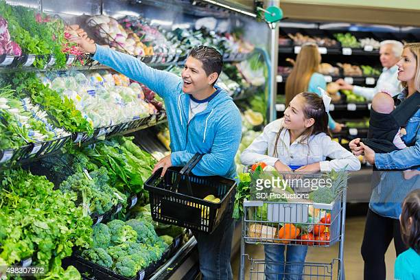 Parents purchasing fresh produce in grocery store with kids