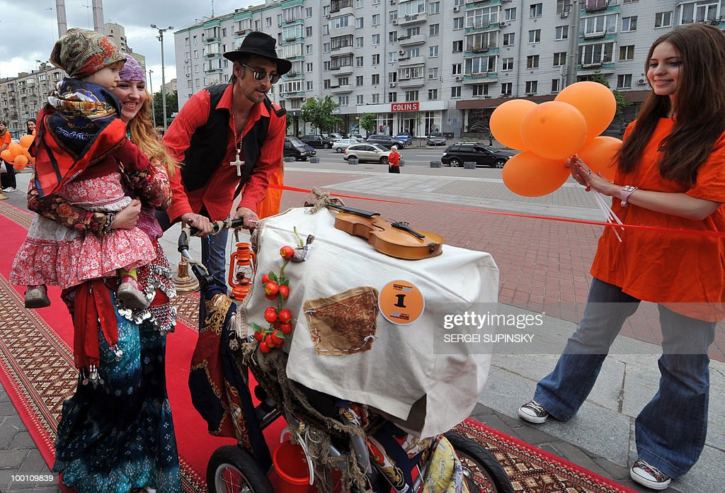 Parents push a hand-made pram decorated as a Gipsy kibitka (a covered cart or sledge) during First Festival of Prams in Kiev on May 21, 2010.