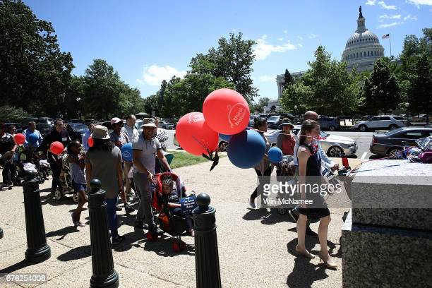 Parents push their children in baby strollers near the US Capitol during a 'Strolling Thunder' event May 2 2017 in Washington DC The event organized...