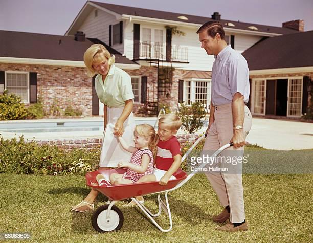 Parents Pushing Children in Wheelbarrow in Backyard