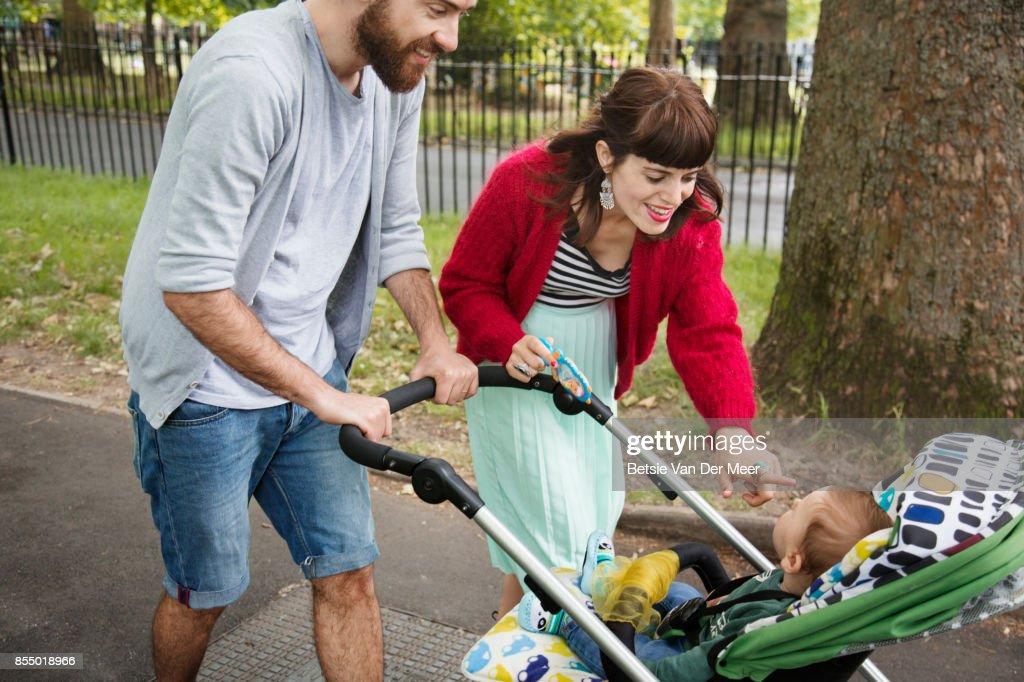 Parents pushing pram, smiling at baby while walking to urban park. : Stock Photo