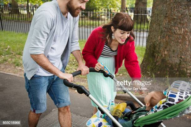 parents pushing pram, smiling at baby while walking to urban park. - carriage stock pictures, royalty-free photos & images