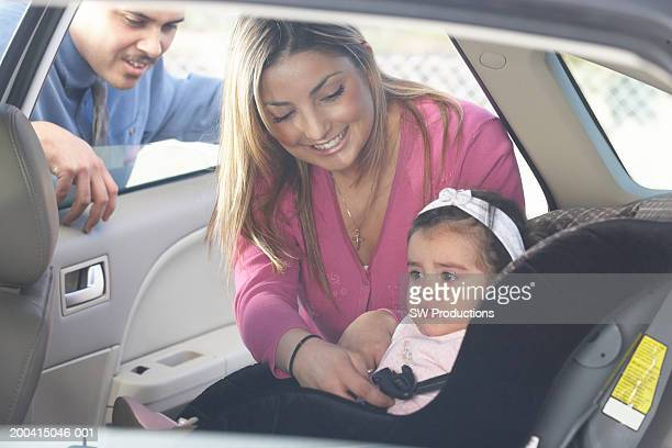 parents putting baby girl (12-15 months) in car seat - 12 23 months stock pictures, royalty-free photos & images