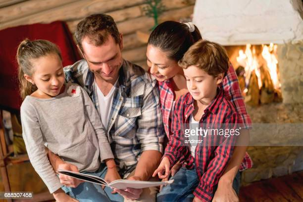 Parents reading a book to their kids in their cozy home