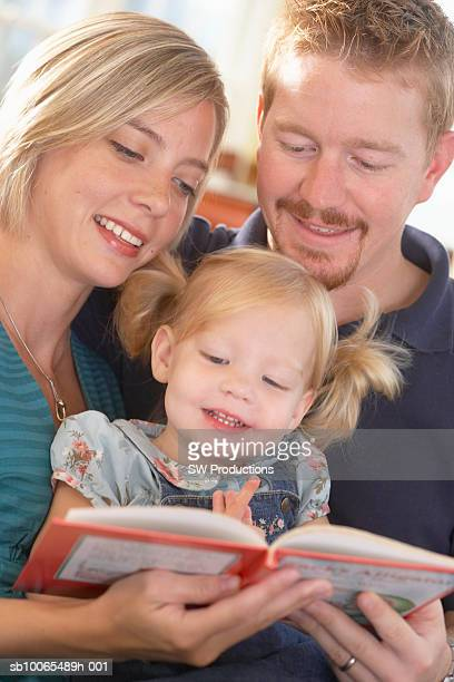 parents reading book to daughter (2-3 years), close-up - 25 29 years stock pictures, royalty-free photos & images