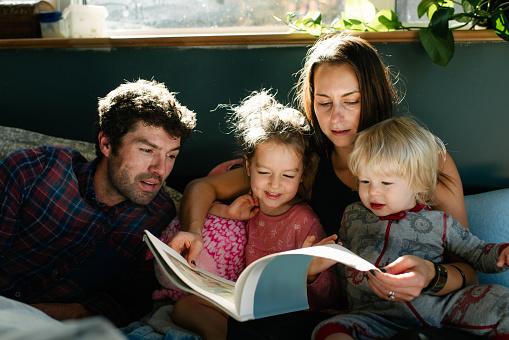 Parents reading to children in bed - gettyimageskorea