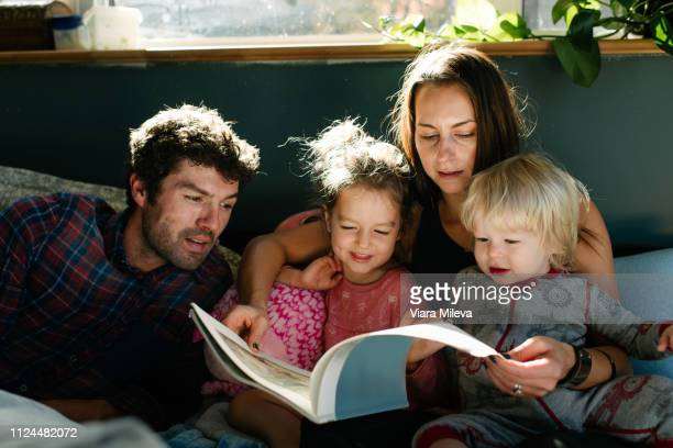 parents reading to children in bed - famiglia con due figli foto e immagini stock