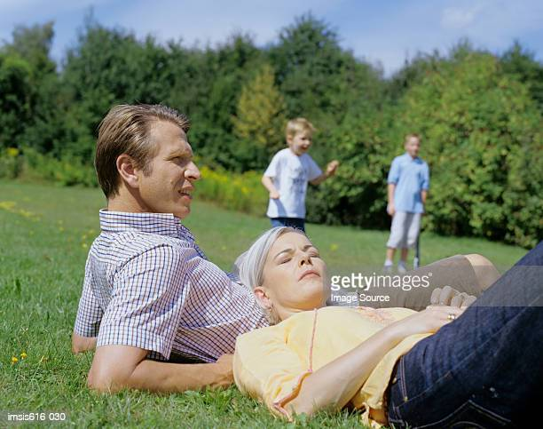 parents relax while boys play. - down blouse stockfoto's en -beelden