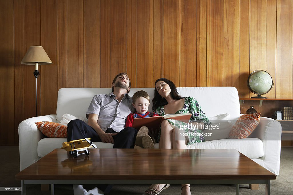 Parents relaxing on couch , in living room, while son (3-5) reads : Stock Photo