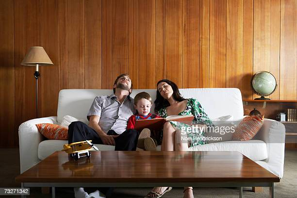 Parents relaxing on couch , in living room, while son (3-5) reads