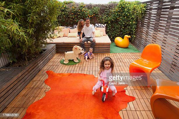 Parents relaxing outdoor with children playing on patio
