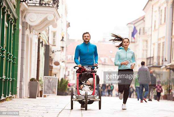 parents running with child in stroller in the city - cochecito para niños fotografías e imágenes de stock