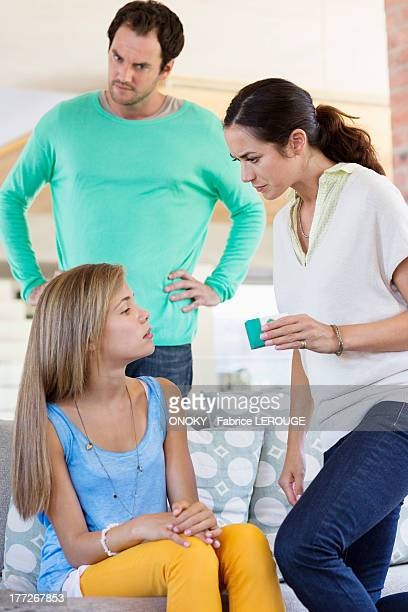 parents scolding their daughter at home - arms akimbo stock pictures, royalty-free photos & images