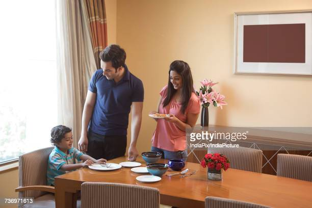 Parents serving food to son at dinning table