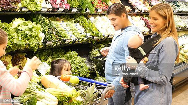 Parents shopping for groceries with three young daughters in supermarket