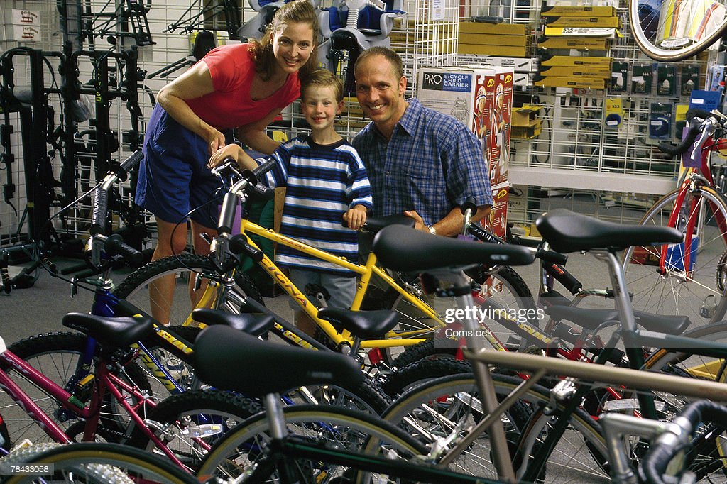Parents shopping for new bike with son : Stockfoto