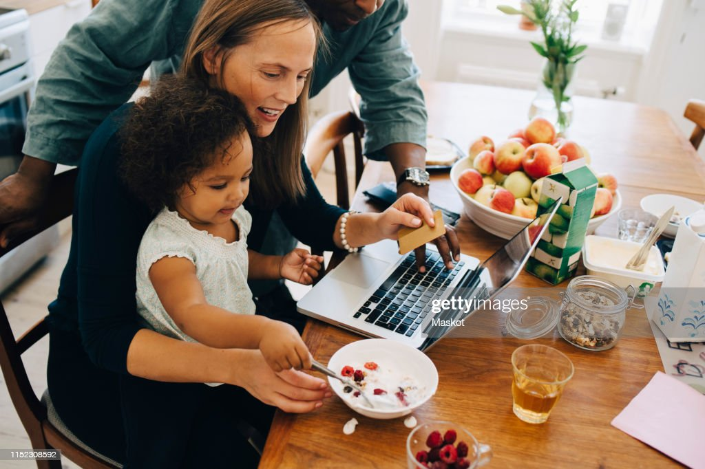 Parents shopping online on laptop while looking at daughter having breakfast in dining room : Stock Photo