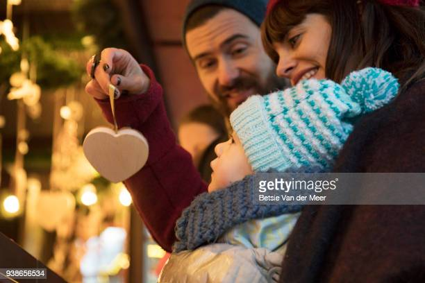Parents show child christmas ornaments at christmas market stall.