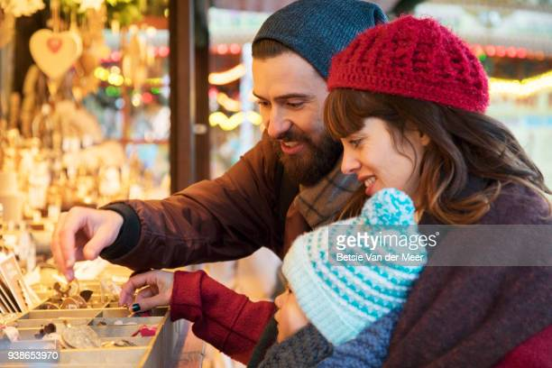 Parents show child ornaments at christmas stall.