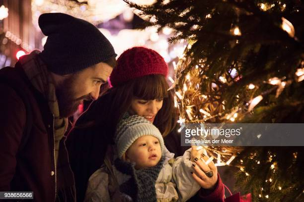 parents show their child the christmas lights on christmas tree in city centre. - feriado evento - fotografias e filmes do acervo