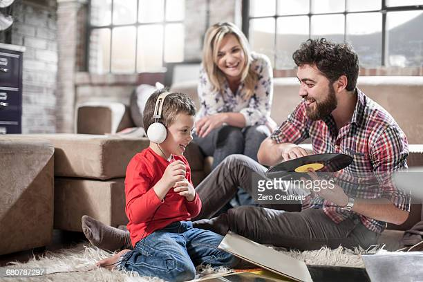 Parents showing vinyl record to son at home