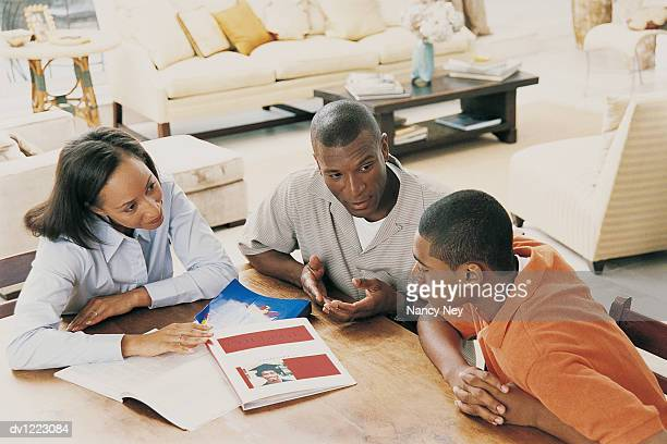 Parents Sitting at a Table at Home Discussing Their Son's Education with Him