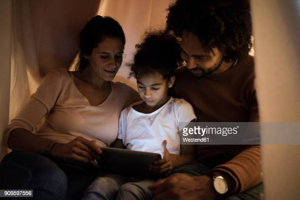 parents sitting in children's room with daughter, looking at digital tablet - daughters of darkness stock pictures, royalty-free photos & images