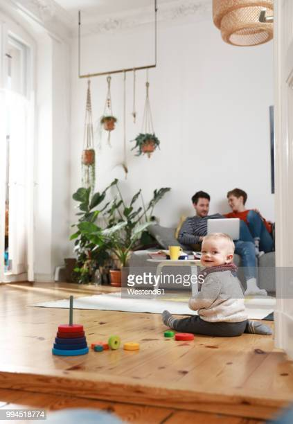 Parents sitting on couch, using laptop, while daughter is playing on the floor