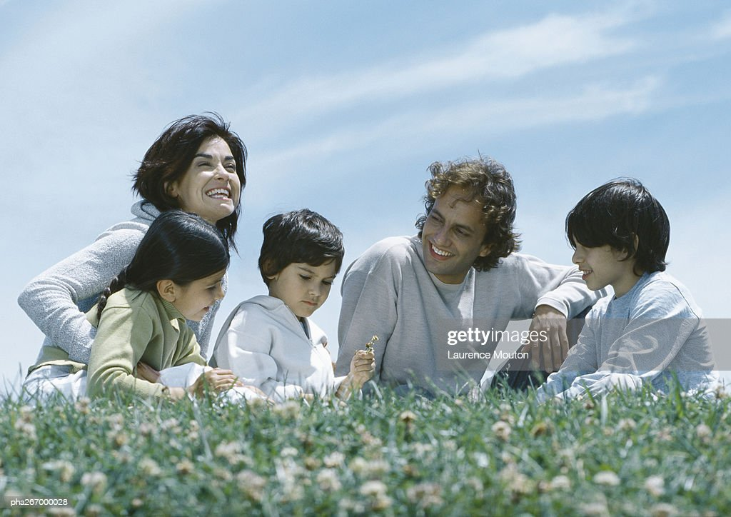 Parents sitting with boys and girl on grass : Stock Photo