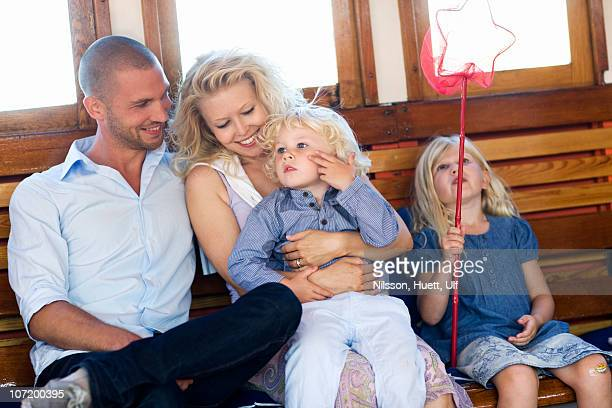 Parents sitting with children, smiling