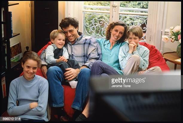 parents sitting with three children (5-12) in front of television - nordeuropäischer abstammung stock-fotos und bilder