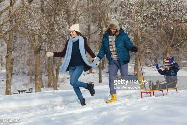 Parents sledging their son in the winter forest