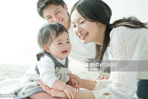 Parents smiling and looking at baby girl