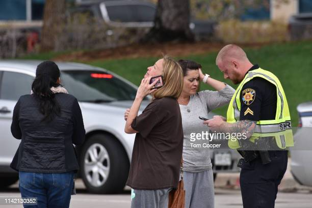 Parents speak with a police officer at the scene of a shooting in which at least seven students were injured at the STEM School Highlands Ranch on...