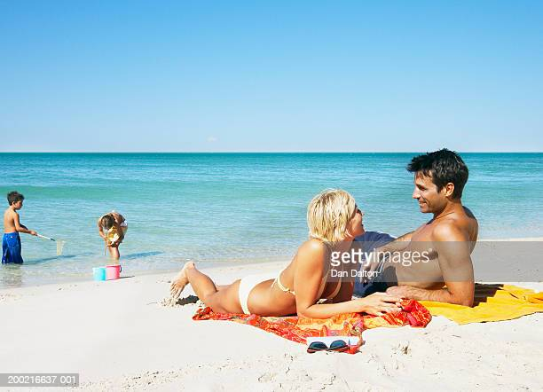 Parents sunbathing, while son and daughter (7-9) play on shore