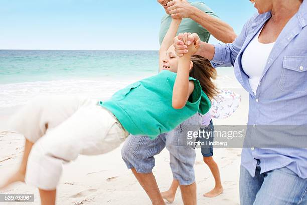 Parents swinging child on the beach