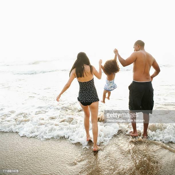Parents swinging daughter between them on beach