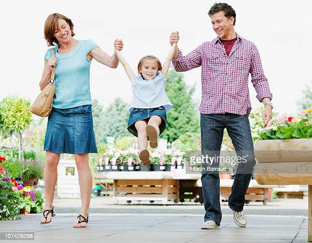 parents swinging daughter in nursery - mom flirting 個照片及圖片檔